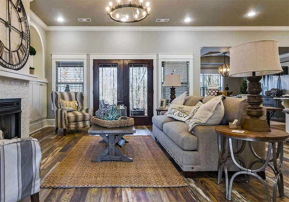 Living room with a gray sofa, striped wingback chairs, and a brick fireplace adorned with an oversized wall clock.