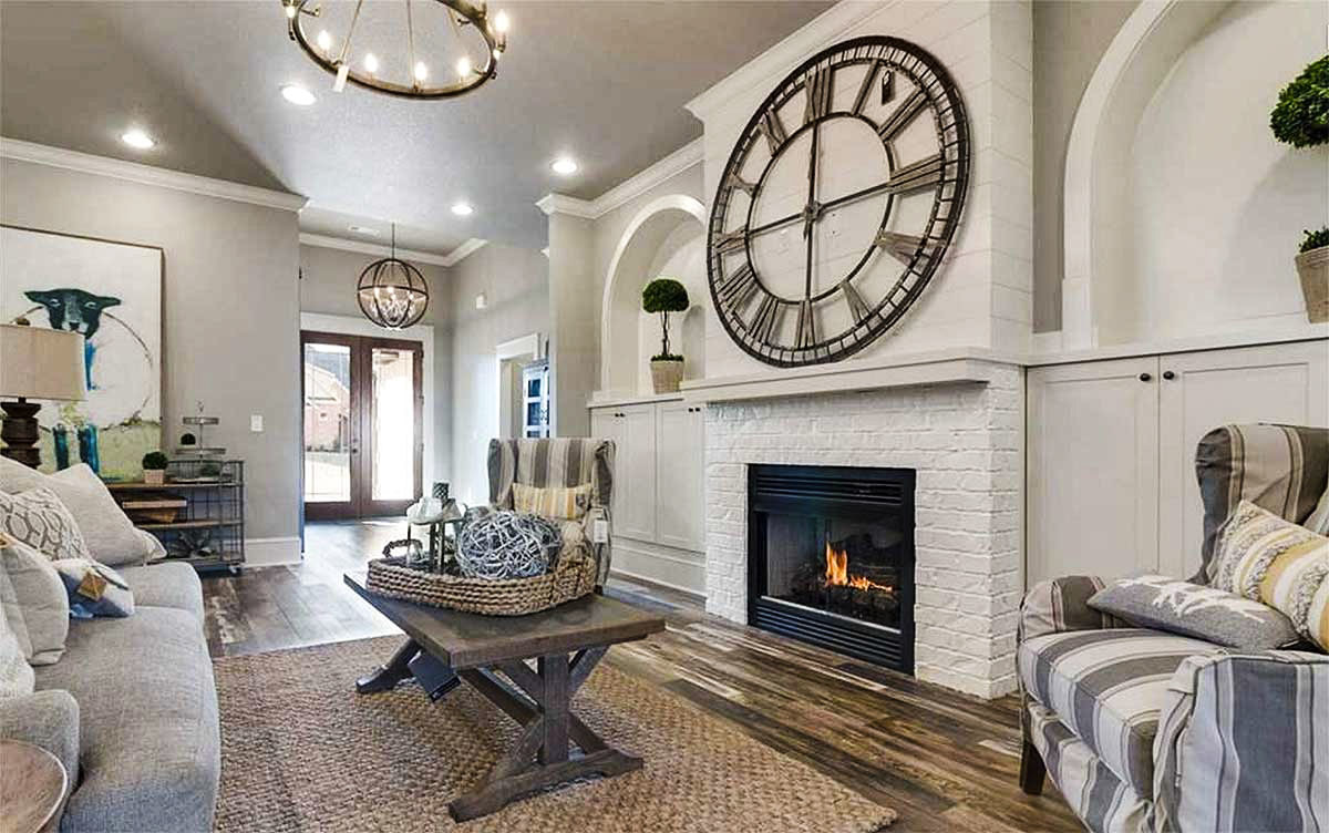 The living room is brightened by a round chandelier and recessed ceiling lights fitted on the vaulted ceiling.