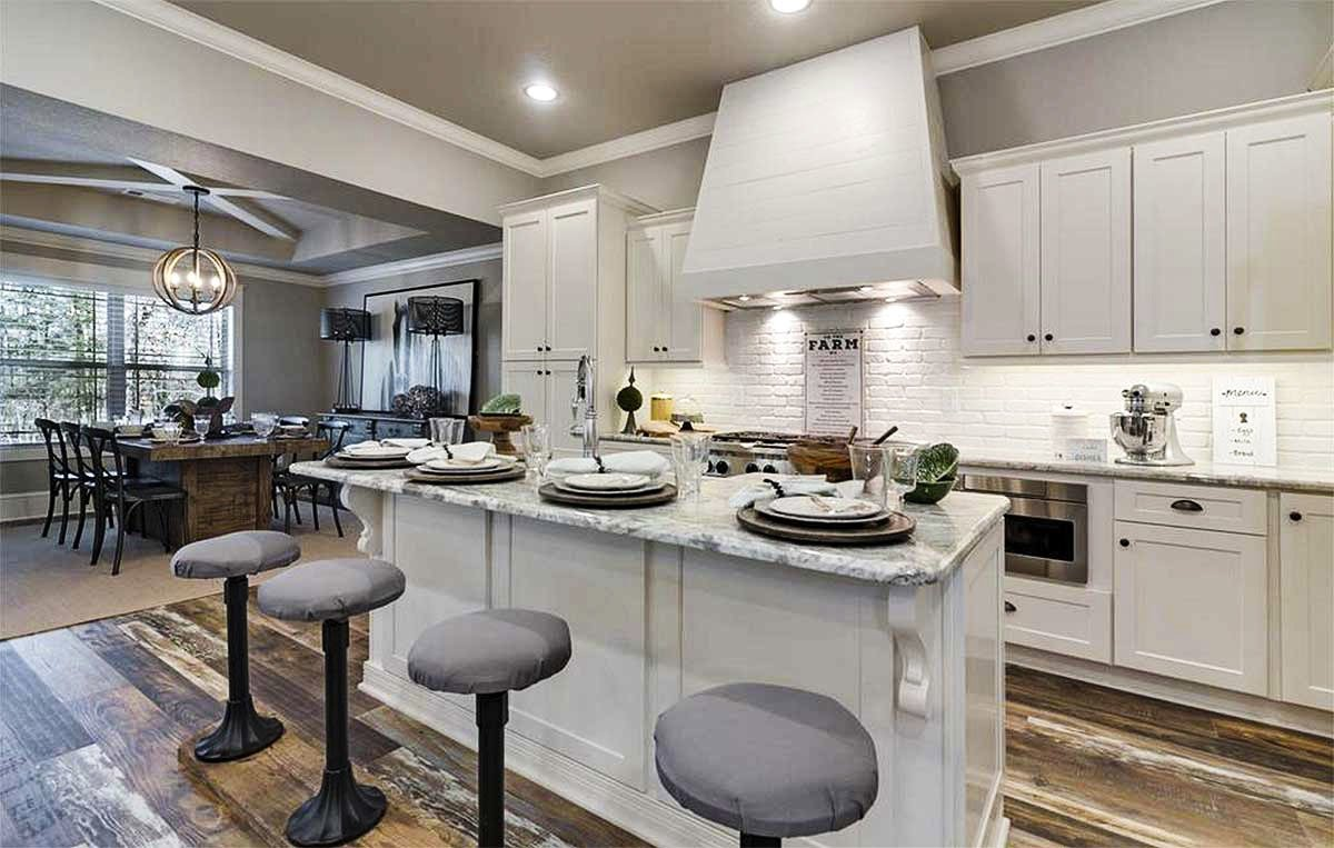 Kitchen with white cabinetry, stainless steel appliances, and a granite top island lined with round bar stools.