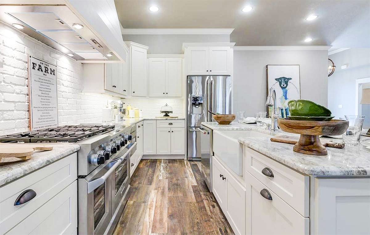 The kitchen island is fitted with a farmhouse sink, a gooseneck faucet, and a dishwasher.