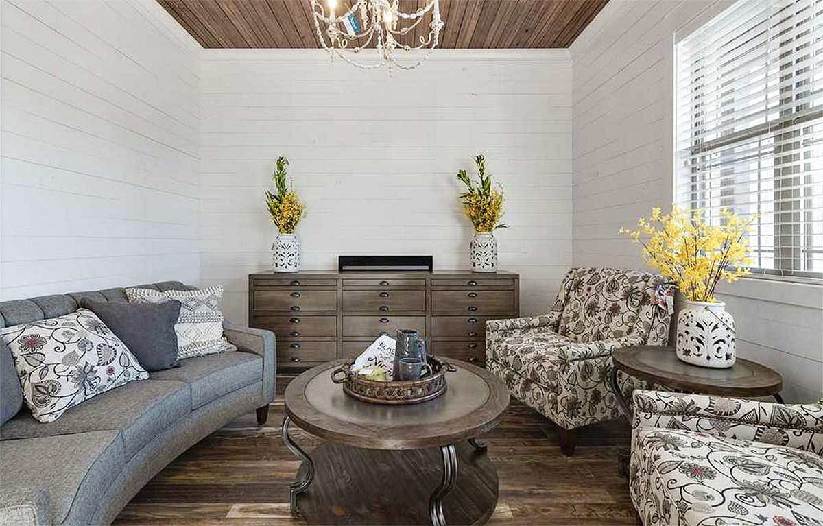 Sitting room with a wooden dresser, floral armchairs, and a curved sectional surrounding the round coffee table.