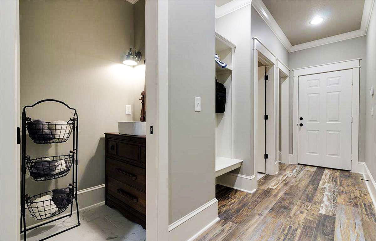 Mudroom with built-in storage and a powder bath with a wrought iron shelving unit.