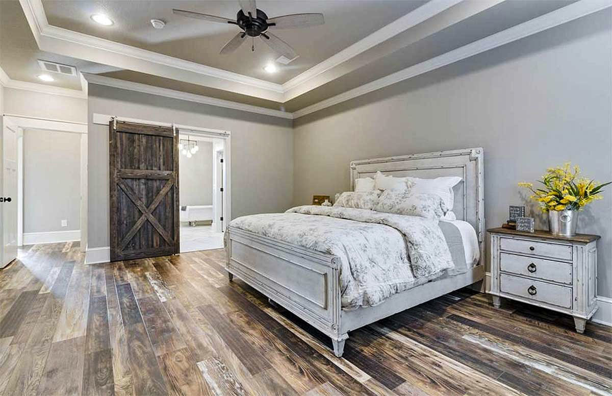A rustic barn door on the left side opens to the primary bathroom.