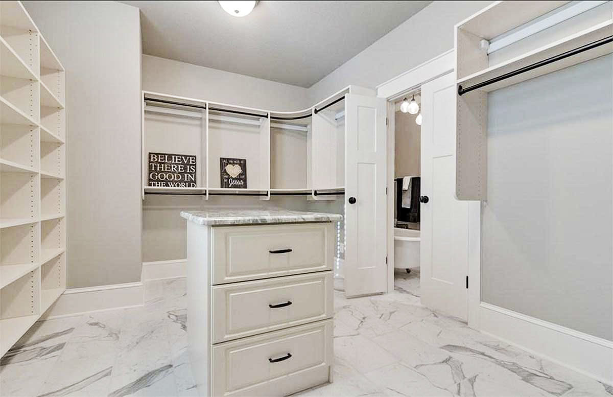 Walk-in closet with built-in shelves and a center island with marble countertop matching with the tiled flooring.