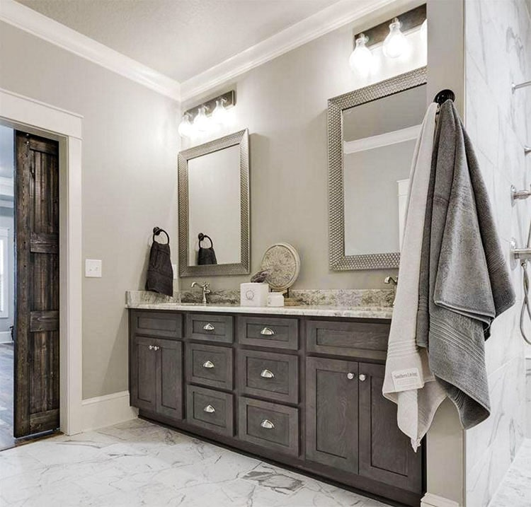 The primary bathroom features a double sink vanity paired with framed mirrors and glass sconces.