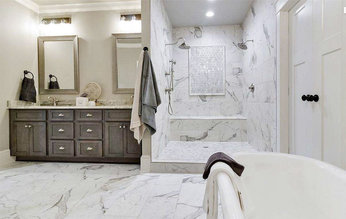 Walk-in shower with two shower heads and a tiled bench along with a freestanding tub complete the primary bathroom.