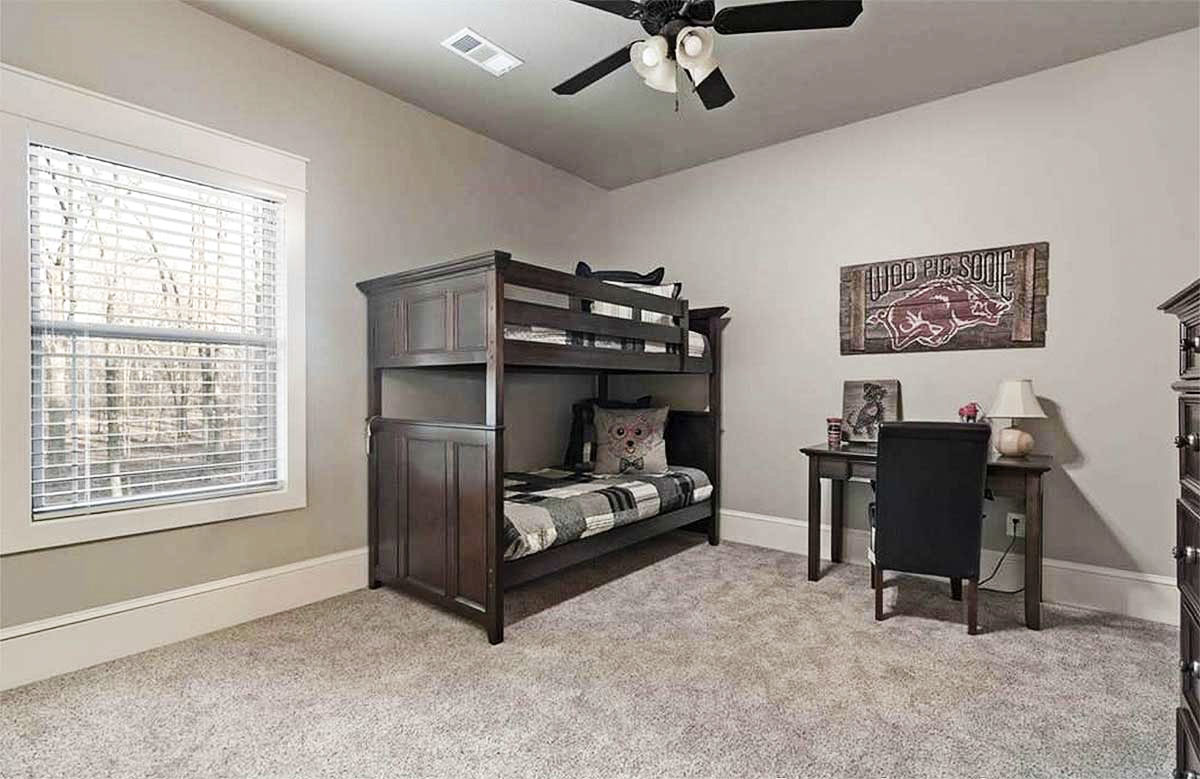 Another bedroom with a bunk bed and a dark wood desk over carpet flooring.