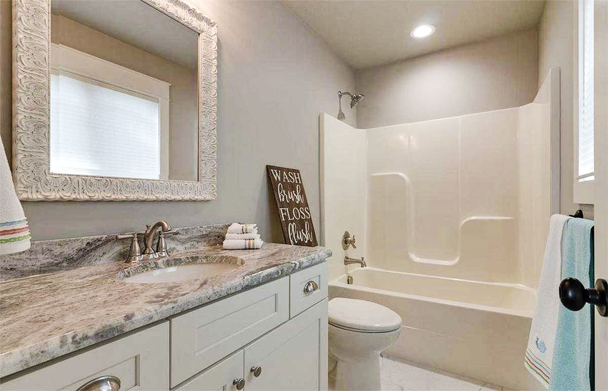 This bathroom is equipped with a sink vanity, a toilet, and a shower and tub combo.