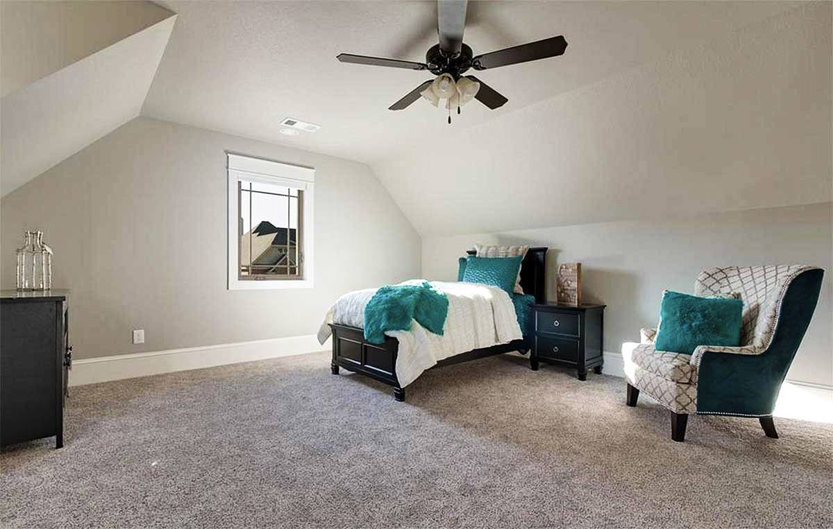 Bonus room with a vaulted ceiling, carpet flooring, a patterned armchair, and a dark wood bed.