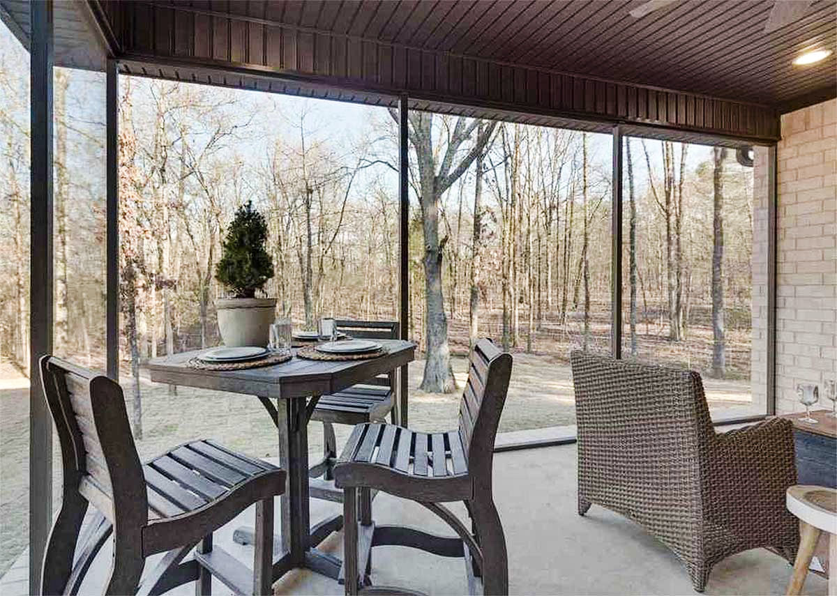 Screened porch furnished with a wicker sofa, a wooden dining table, and matching chairs.