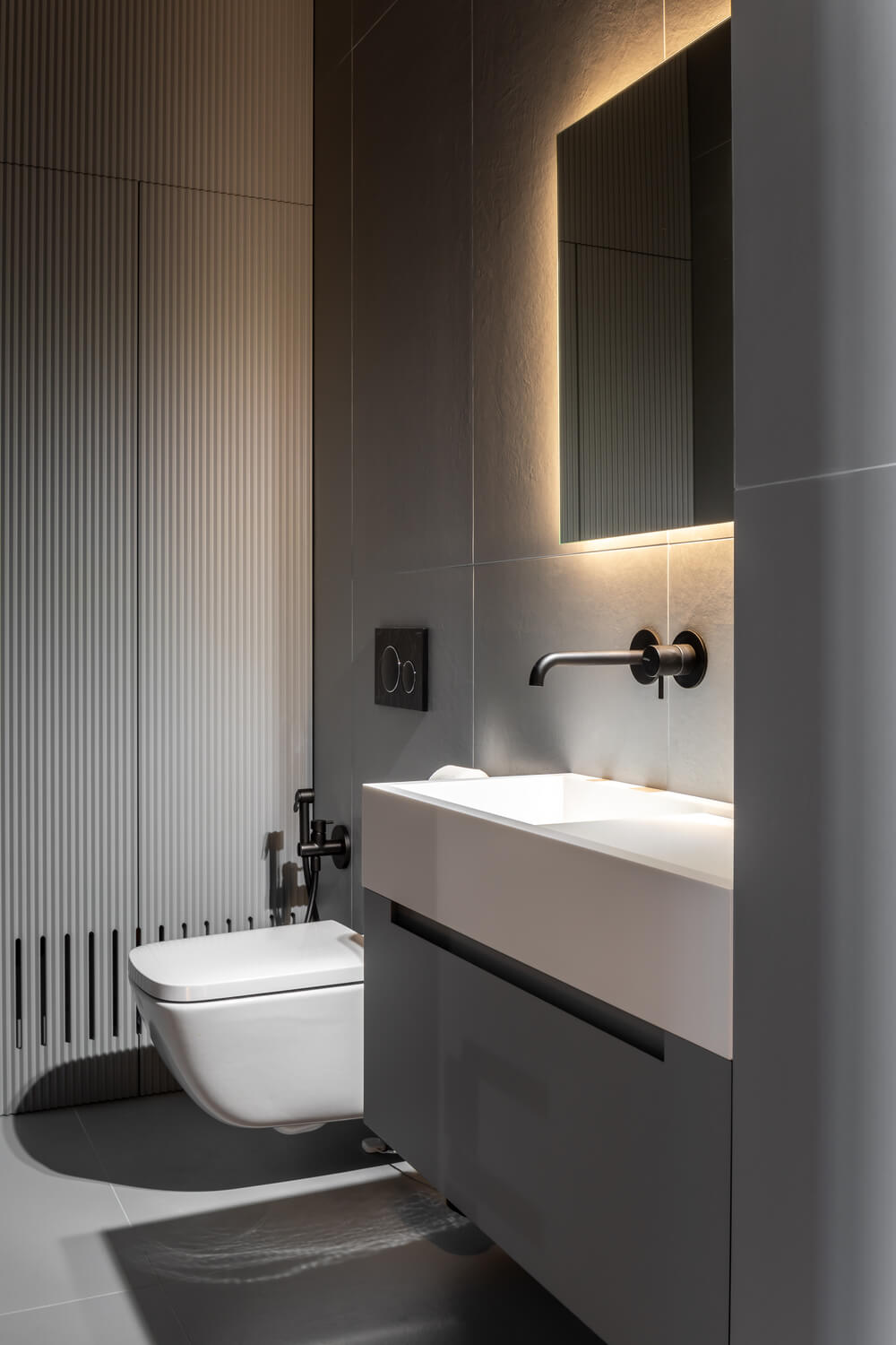 This other bathroom has a modern floating vanity beside the floating toilet.