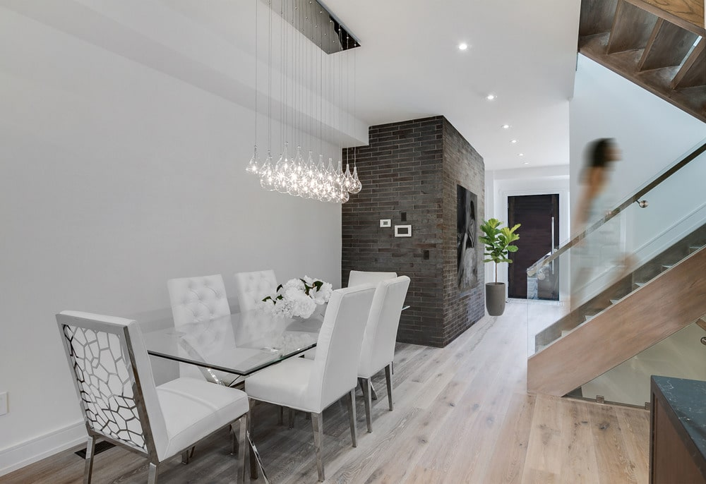 Next to the brick wall is the dining area with bright white walls and ceiling.
