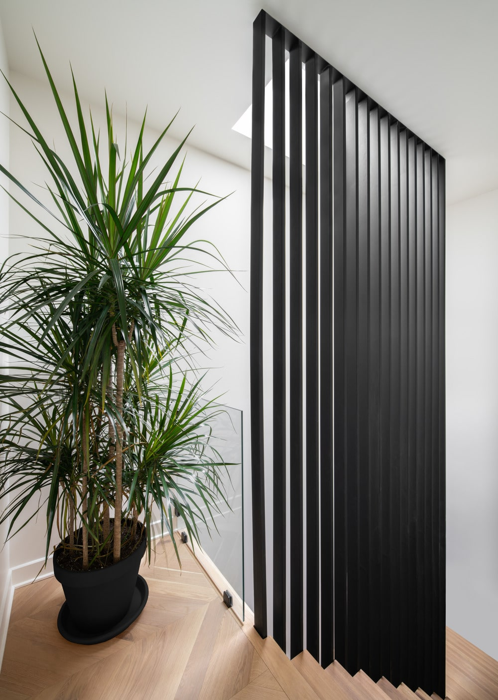 This is a close look at the landing with a black slatted panel on the side adorned with a large potted plant.
