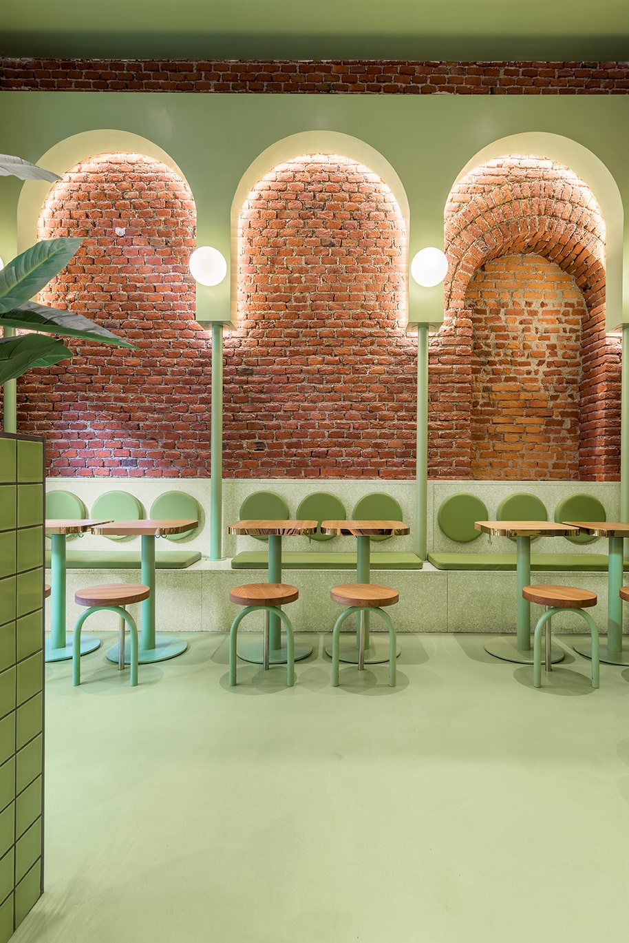 This is another view of the green side of the restaurant with its small wooden tables and small chairs paired with built-in benches on the far side under the red brick wall.