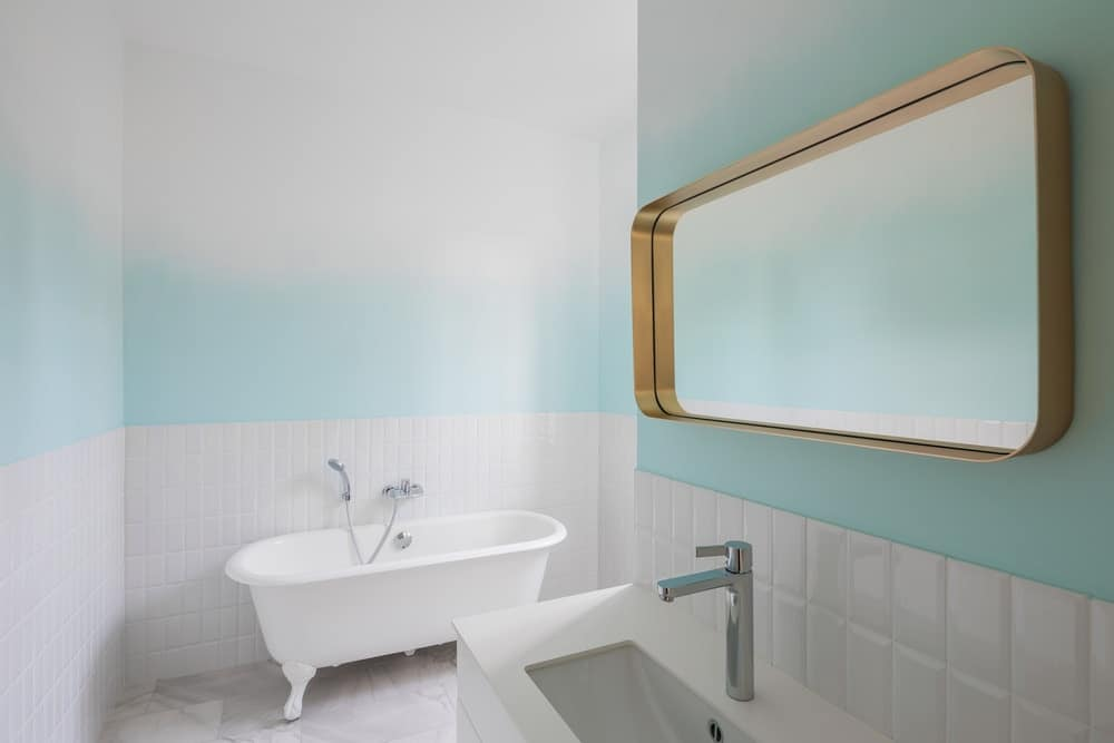 This minimalist bathroom has a white freestanding bathtub, a white sink and white tiles complemented by the streak of pastel tone on the upper walls.