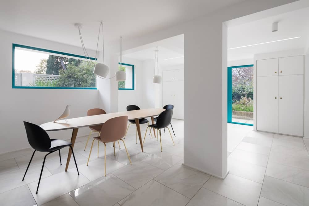 This is a minimalist dining area with white walls and ceiling brightening up the wooden dining set topped with a row of modern white pedant lights.