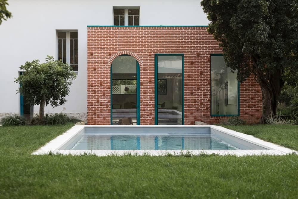This is a simple landscaping that has a grass lawn surrounding a swimming pool supported by concrete. These are then complemented by trees and the brick wall of the house.