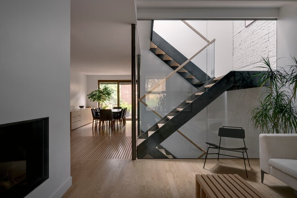 A few steps from the built-in sofa is this modern staircase with glass walls.