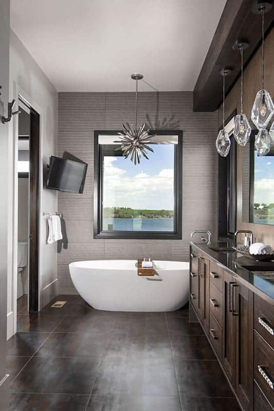 This mountain-style bathroom has a large two-sink dark wooden vanity, a white freestanding bathtub on the far side by the window and a toilet area on the side.