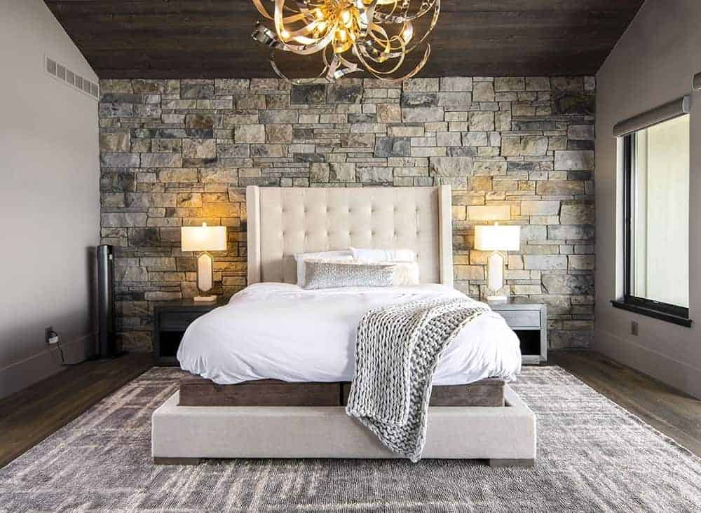 This is a mountain-style primary bedroom with a mosaic textured stone wall behind the beige tufted headboard of the platform bed topped iwth a decorative golden lighting from the dark brown wooden ceiling.