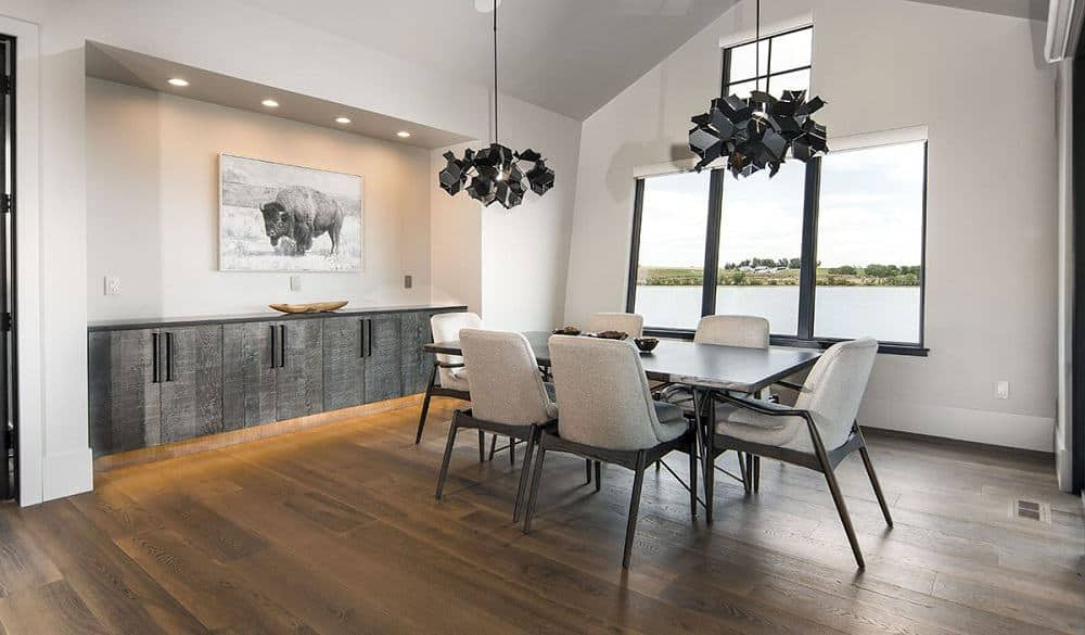 This is a spacious mountain-style dining room with a large glass window on the far wall across from the dining set that has bright beige chairs topped with a couple of decorative lighting.