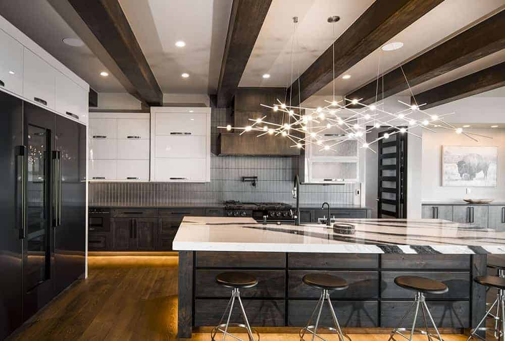 The mountain-style kitchen has a consistent dark wooden tone on its large kitchen island, cabinetry on the far wall and the exposed beams of the ceiling that hangs a large decorative lighting over the kitchen island.
