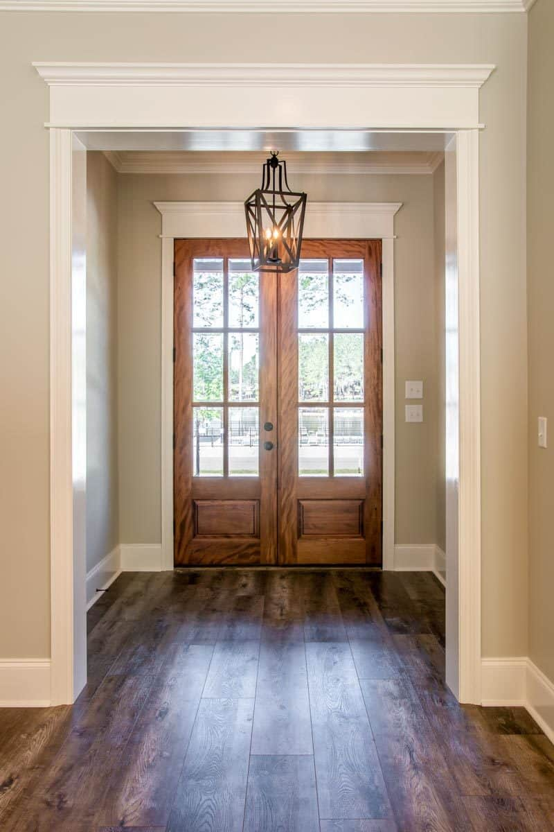 The foyer has a wrought iron pendant and a french entry door that matches the wide plank flooring.