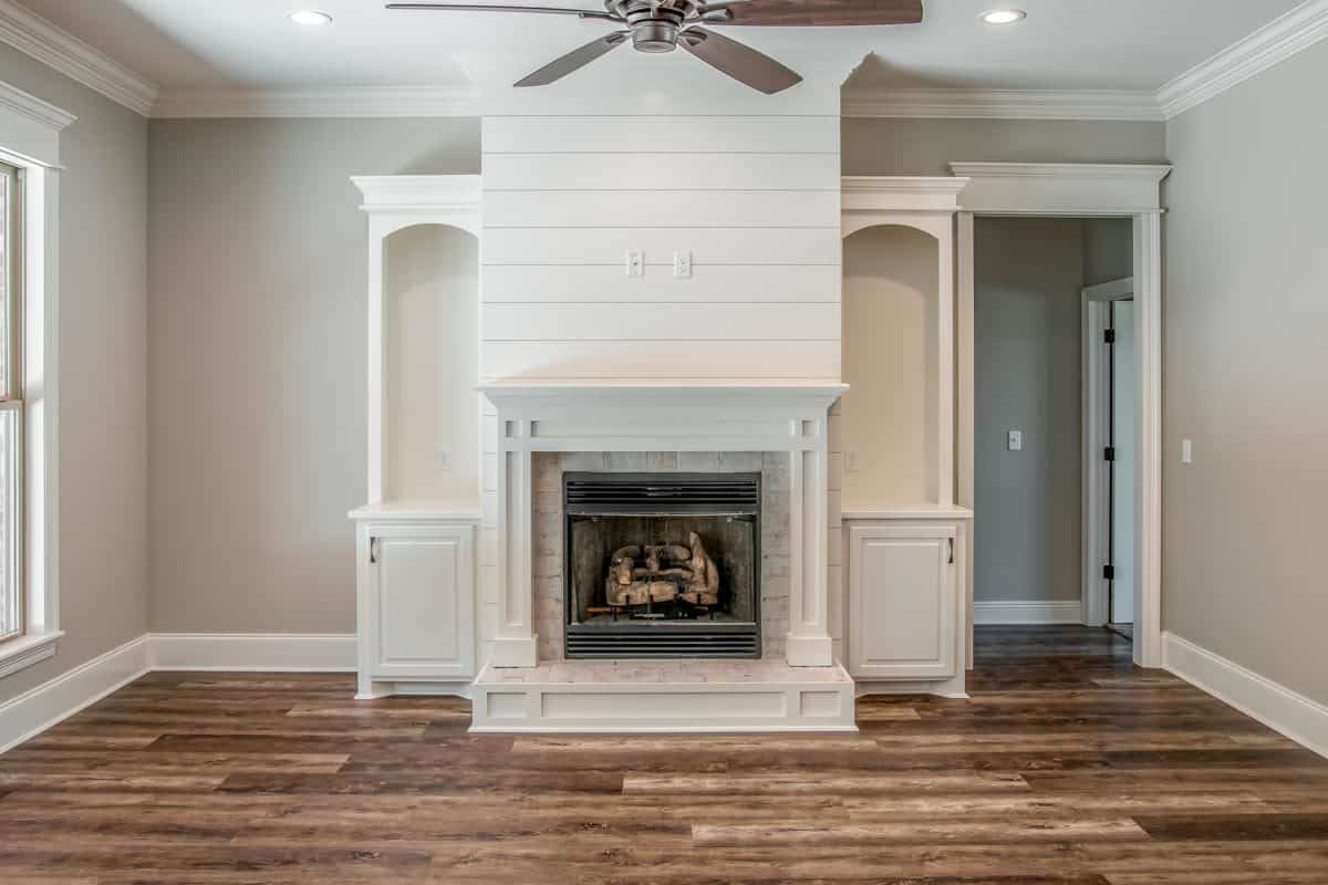 Living room with a ceiling fan and a fireplace flanked by white cabinets.Living room with a ceiling fan and a fireplace flanked by white cabinets.