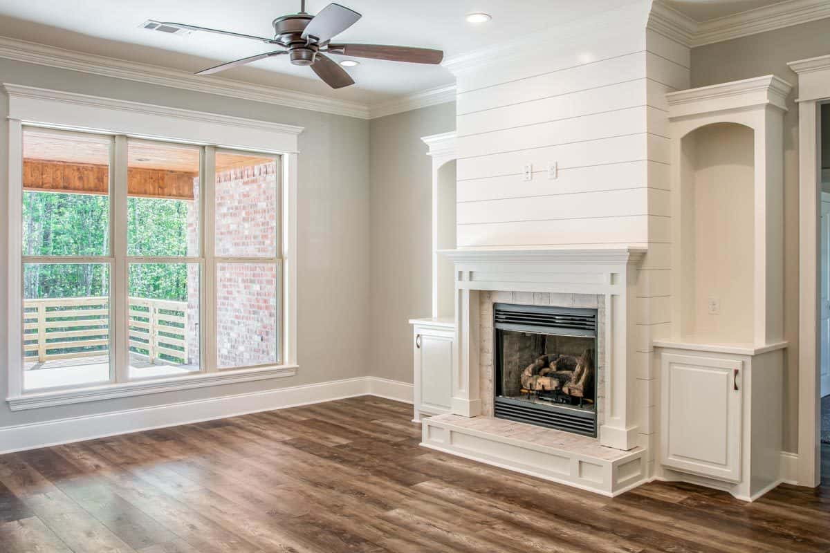 The living room includes a three-paneled window overlooking the back porch.