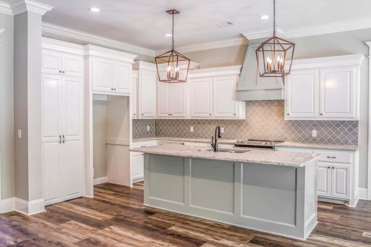 The kitchen offers white cabinetry, stainless steel appliances, and a breakfast island topped with caged pendants.