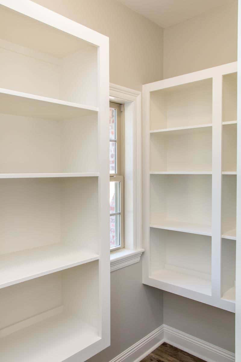 The walk-in pantry is filled with white built-in shelves and a small window.