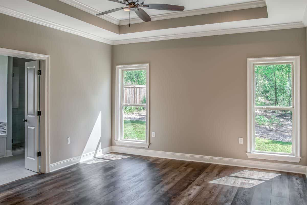 Primary bedroom with wide plank flooring, a tray ceiling, and a double door that opens to the primary bath.
