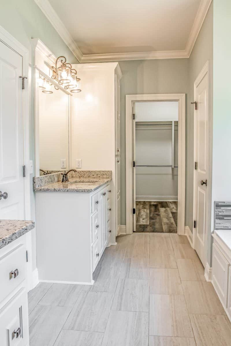 The primary bathroom offers his and her vanities, a toilet room, and a walk-in closet.