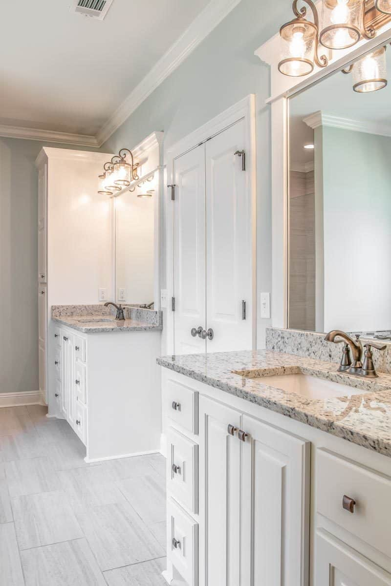 The double vanities are equipped with chrome fixtures, granite countertops, large mirrors, and glass sconces.