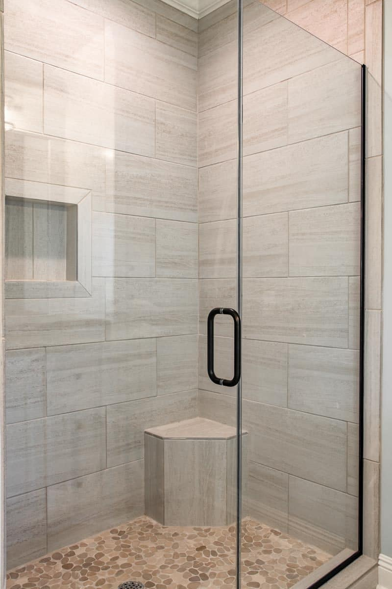 Walk-in shower with an inset shelf, a corner seat, and a glass hinged door.