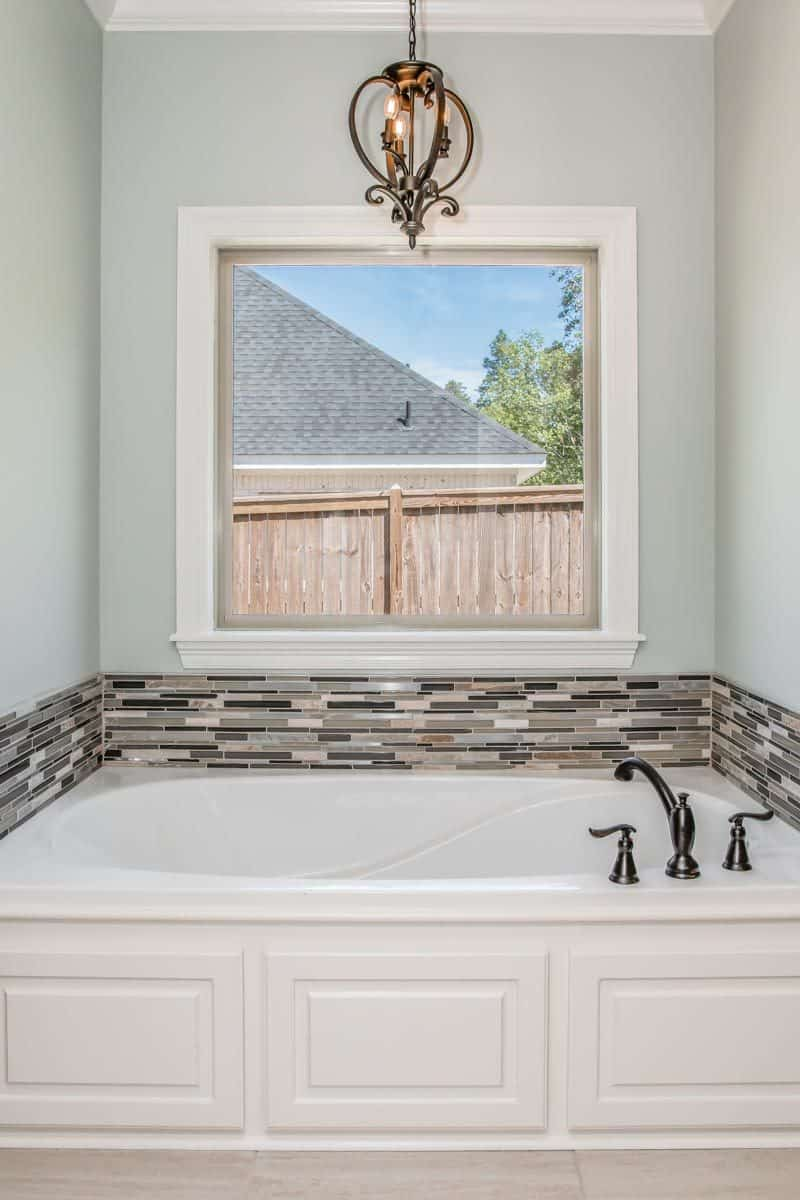 The drop-in bathtub accentuated with a linear mosaic tile backsplash is placed under the picture window.