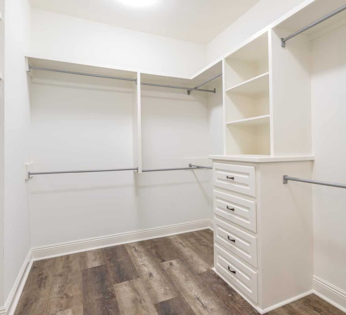 Walk-in closet with hardwood flooring and built-in drawers and shelves blending in with the white walls.