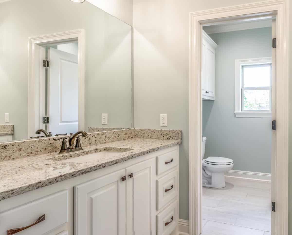 This bathroom offers a toilet room and a single sink vanity paired with a large frameless mirror.