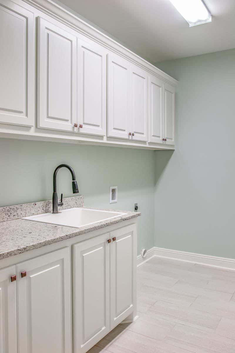 Utility room with white cabinets, granite countertop, and a porcelain sink.