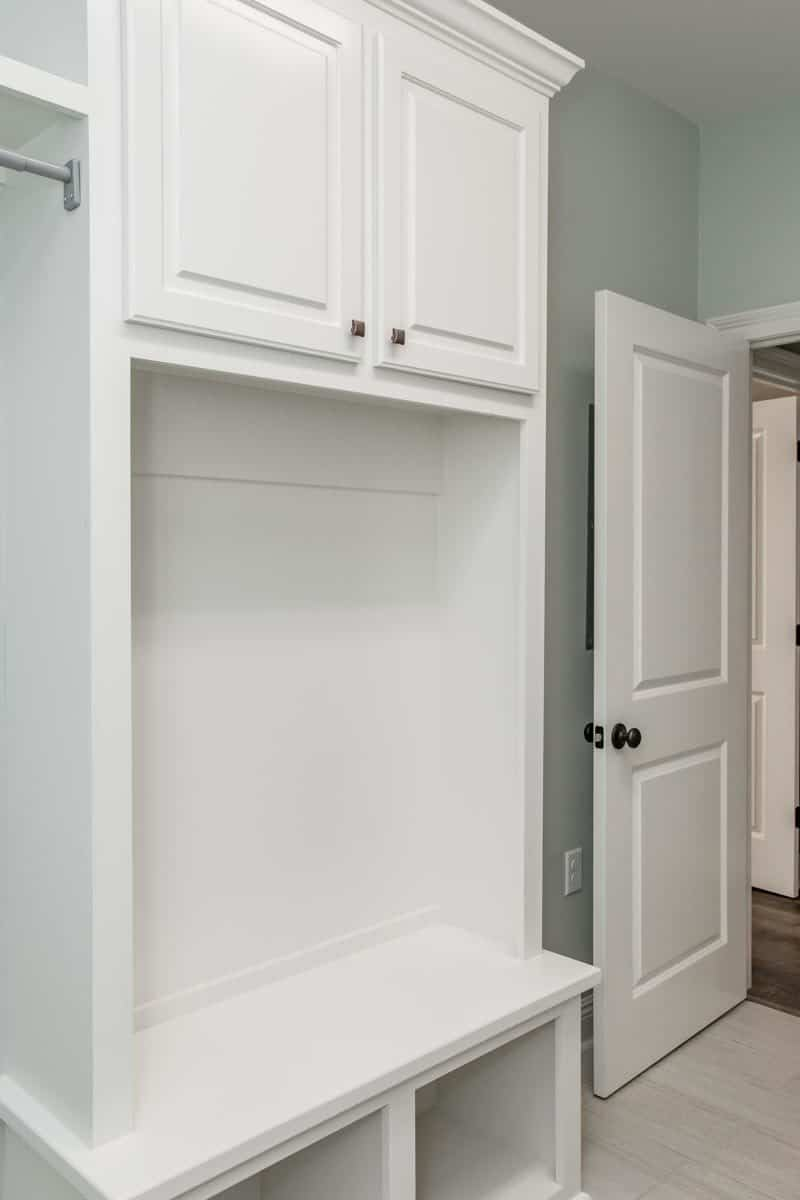 The mudroom features a built-in cabinet with a storage bench.