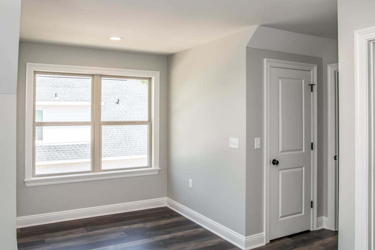 A larger window next to the walk-in closet invites ample natural light in.