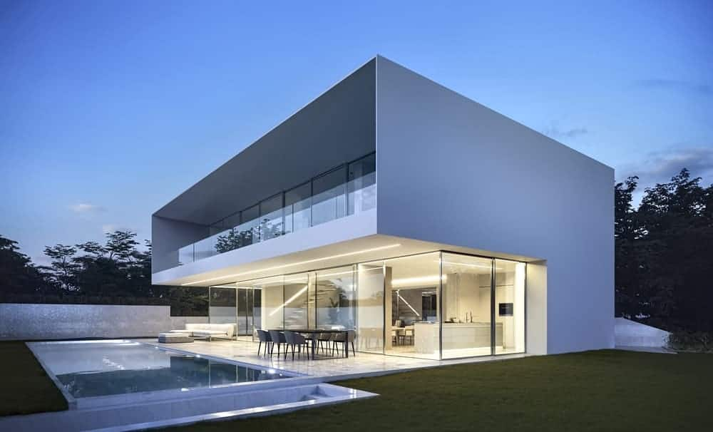 This is an exterior view of the back of the house that has modern white walls and glass walls complemented by the well-manicured grass lawn and swimming pool area.