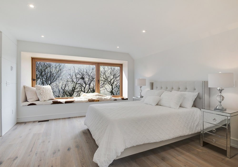 This bedroom has a large white bed and a reading nook below the window on the far side with a built-in bench under the glass windows.