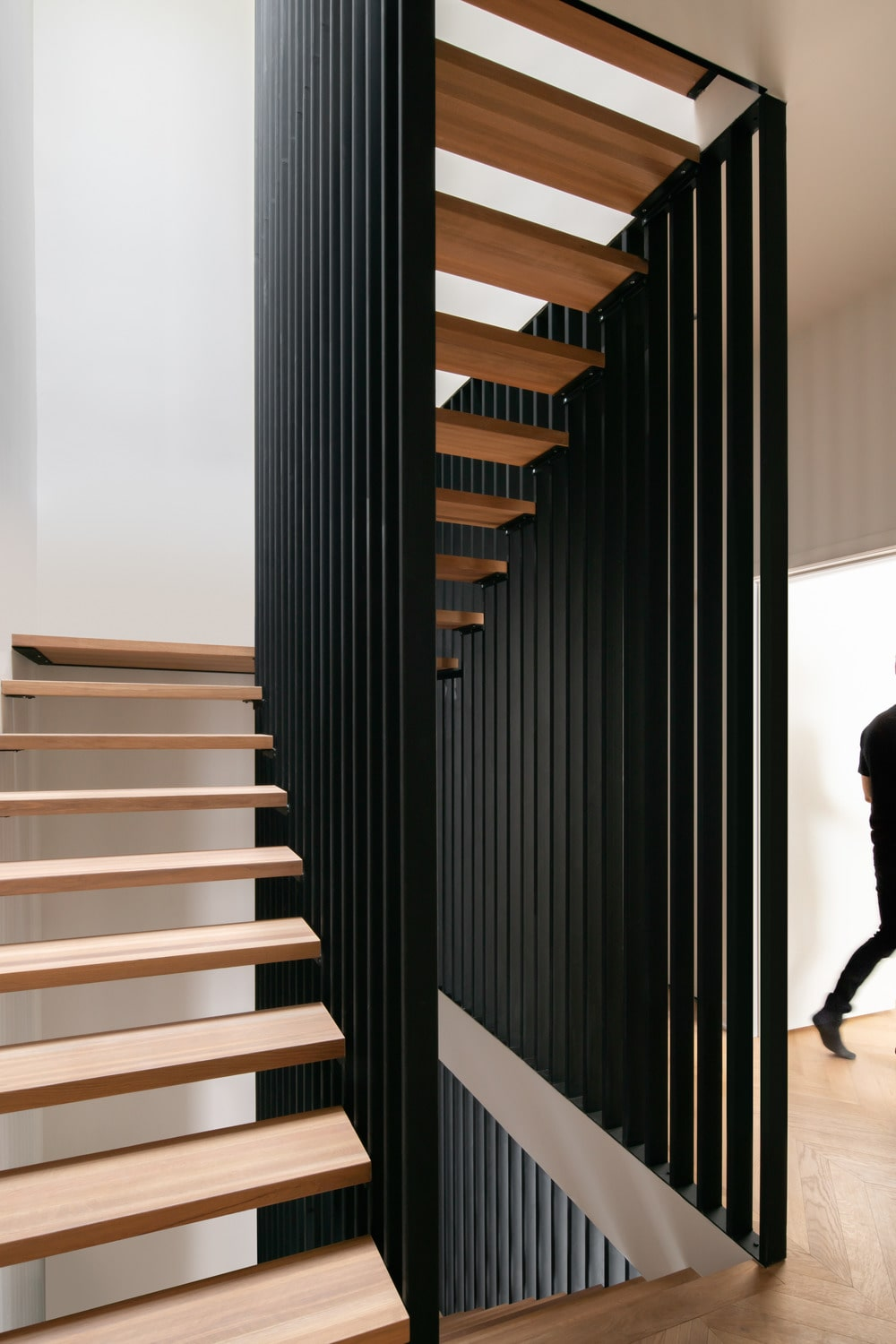 The black structures of the staircase give a nice contrast for the light wooden tone of the steps and hardwood flooring.