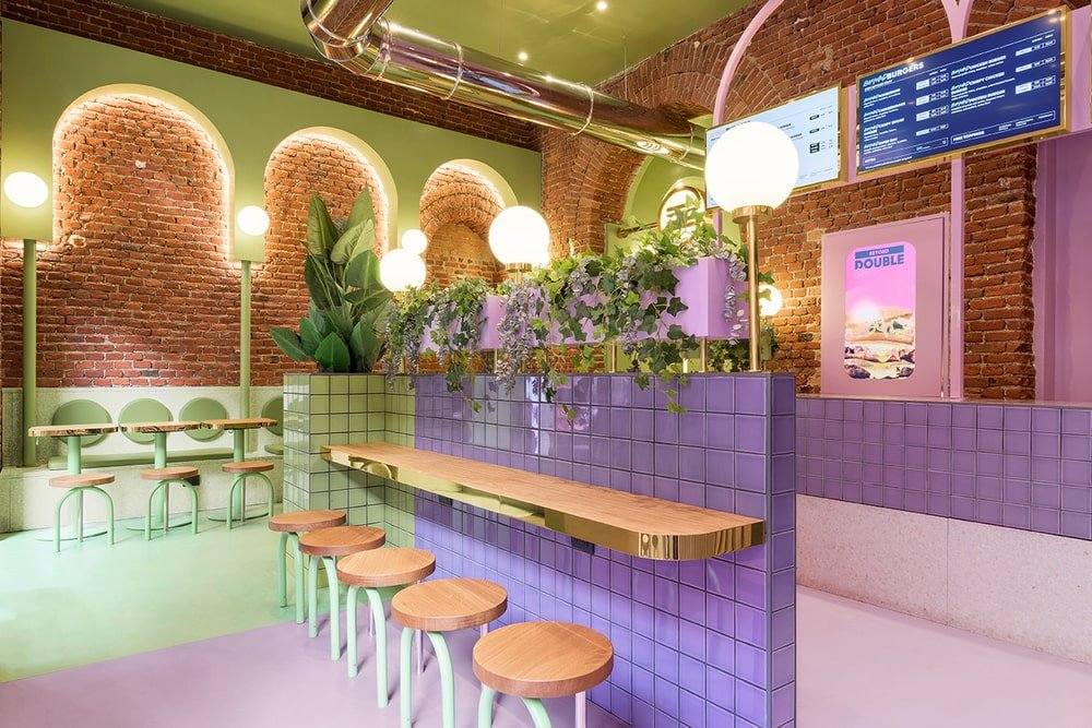 This is a close look at a space-saving divider of the restaurant with green and purple tiles on it and has a built-in bar paired with stools.