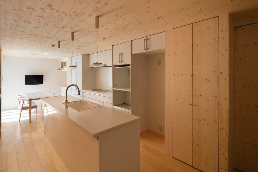 This is a close look at the long and narrow kitchen with a minimalist design of wooden panels and white kitchen island topped with modern pendant lights.
