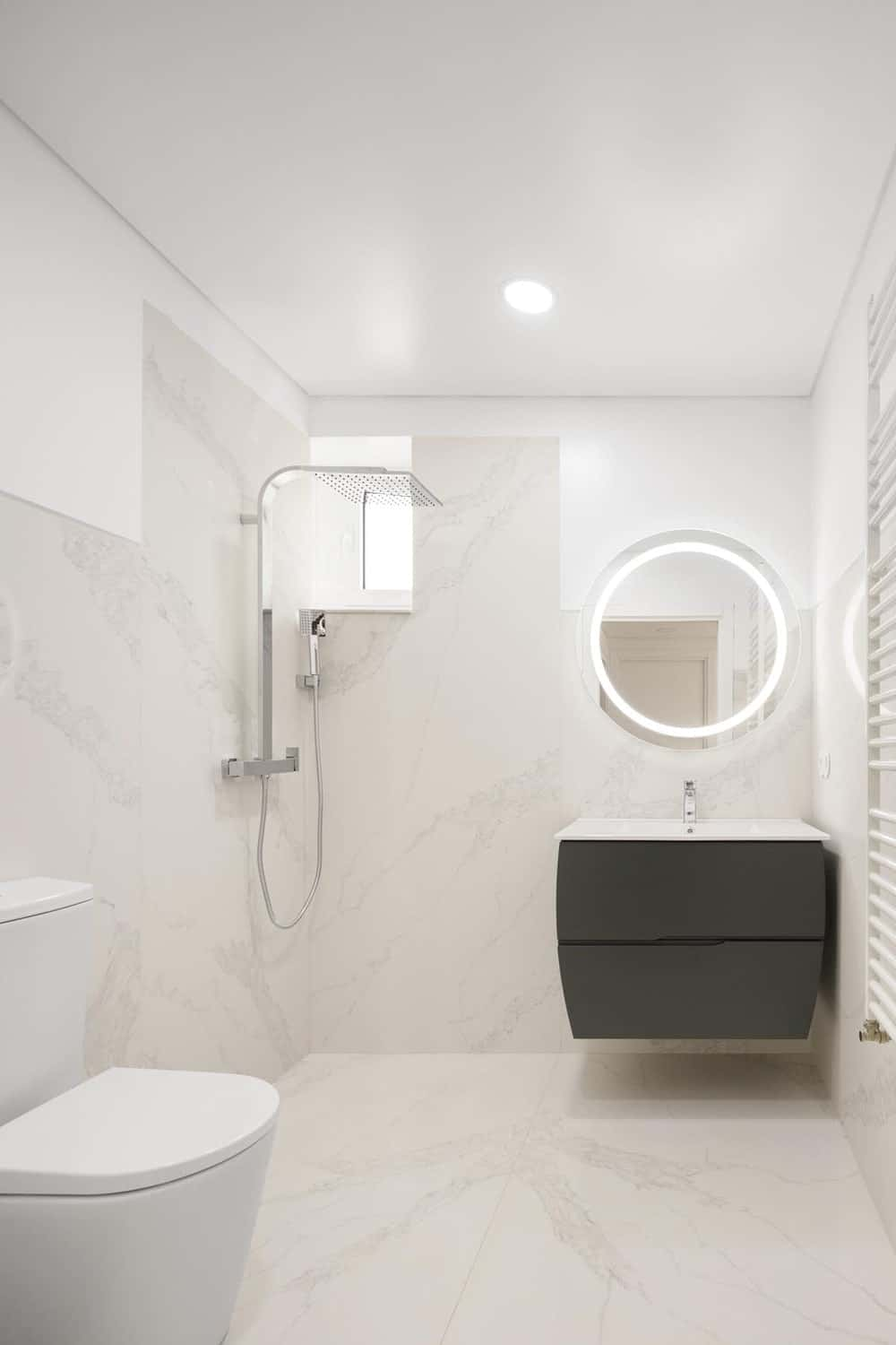 This is a minimalist bathroom that has consistent bright beige marble on its floor and walls. This makes the black floating vanity stand out topped with a round vanity mirror.