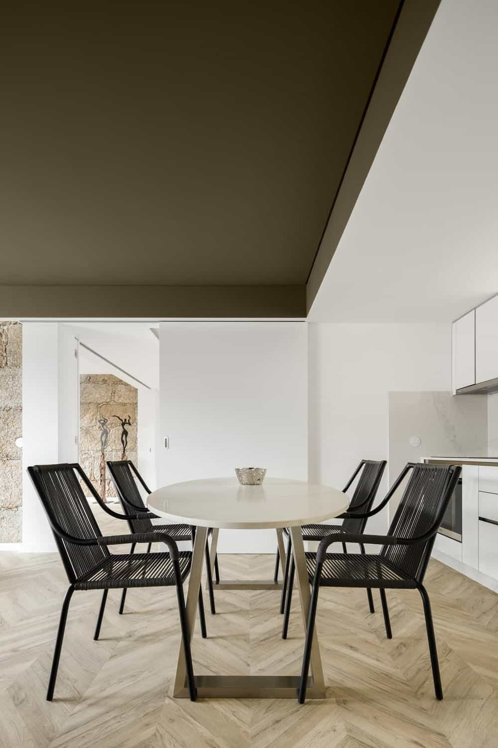 This is a close look at the dining area with a white marble dining table contrasted by the black dining chairs that stand out against the beige flooring.