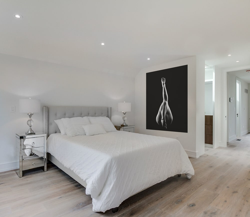 On the other side of the white bed is a large wall-mounted artwork that stands out against the surrounding white walls and white ceiling.