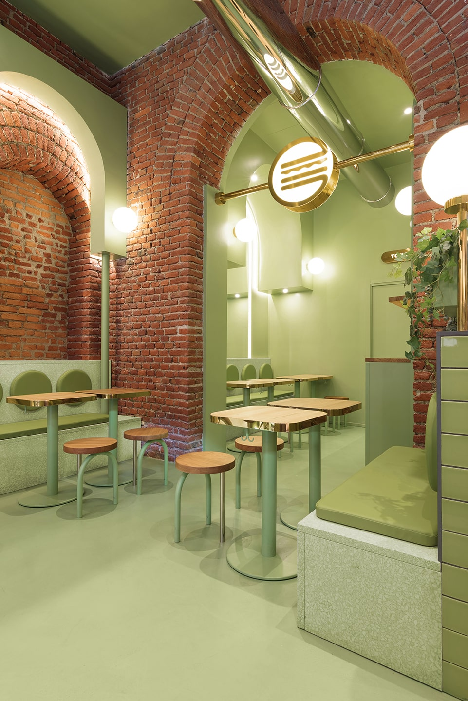 This is a close look at the green edge of the restaurant with its tall archway, red brick wals and contrasting green tone on its floor, wall and ceiling that has exposed vents.
